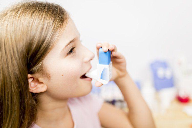 Girl using inhaler to manage asthma symptoms
