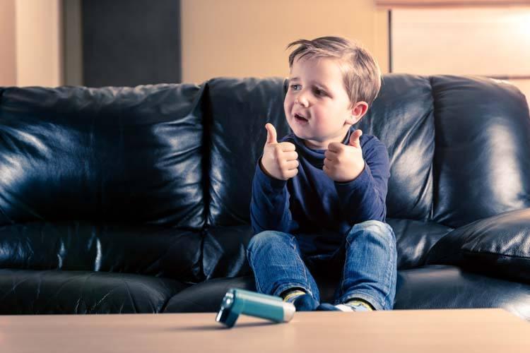 Child with salbutamol inhaler giving thumbs-up