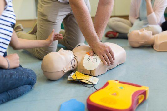 First Aiders practising CPR with a defibrillator during and AED training course