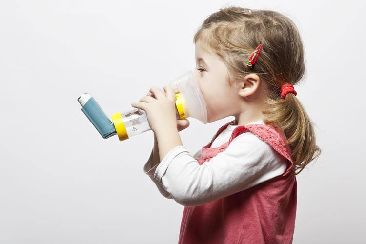 Child using a spacer to take her asthma medication
